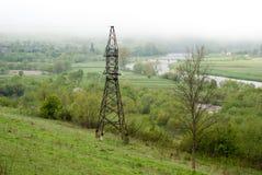 Γραμμή μετάδοσης tower Γιγαντιαίο σύννεφο γέφυρα πέρα από τον ποταμό ομιχλώδης καιρός Στοκ Φωτογραφία