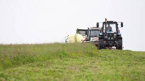Γραμμή μηχανών γεωργίας που οδηγούν στον τομέα χλόης στο αγρόκτημα απόθεμα βίντεο