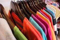 Γραμμή πολυ χρωματισμένων ενδυμάτων στις ξύλινες κρεμάστρες στο κατάστημα Πώληση Στοκ Φωτογραφία