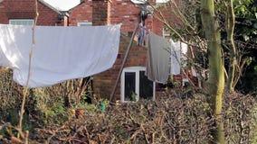 Γραμμή πλύσης - κάλτσες, φύλλα, ενδύματα & πετσέτες που κρεμά στο βικτοριανό σπίτι καλλιεργήστε - ζωή κωμοπόλεων/πόλεων απόθεμα βίντεο