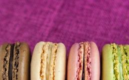 Γραμμή macaroons στο ρόδινο τραπεζομάντιλο γιούτας Στοκ εικόνα με δικαίωμα ελεύθερης χρήσης