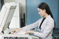 Γραμματέας γυναικών που χρησιμοποιεί τη μηχανή αντιγράφων στο γραφείο Στοκ φωτογραφία με δικαίωμα ελεύθερης χρήσης