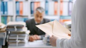 Γραμματέας που φέρνει έναν φάκελο στον προϊστάμενό της στοκ εικόνα με δικαίωμα ελεύθερης χρήσης