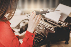 Γραμματέας στην παλαιά γραφομηχανή με το τηλέφωνο Νέα γυναίκα που χρησιμοποιεί ty Στοκ εικόνα με δικαίωμα ελεύθερης χρήσης