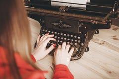 Γραμματέας στην παλαιά γραφομηχανή με το τηλέφωνο Νέα γυναίκα που χρησιμοποιεί ty Στοκ Εικόνες