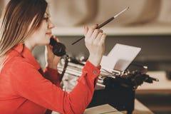 Γραμματέας στην παλαιά γραφομηχανή με το τηλέφωνο Νέα γυναίκα που χρησιμοποιεί ty Στοκ φωτογραφία με δικαίωμα ελεύθερης χρήσης