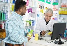 Γραμμωτός κώδικας προϊόντων ` s ανίχνευσης φαρμακοποιών ενώ πελάτης που στέκεται στο κοβάλτιο στοκ φωτογραφίες
