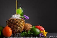 Γρανάτης, καρύδα, carambola και εσπεριδοειδή σε ένα μαύρο υπόβαθρο Μια σύνθεση των εξωτικών φρούτων και multifruit του χυμού Στοκ Εικόνες