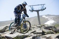 ΓΡΑΝΑΔΑ, ΙΣΠΑΝΙΑ - 30 ΙΟΥΝΊΟΥ: Άγνωστος δρομέας στον ανταγωνισμό του φλυτζανιού DH 2013, οροσειρά Νεβάδα ποδηλάτων του Bull ποδηλά Στοκ Φωτογραφίες