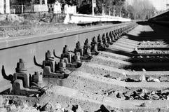 γραπτά μπουλόνια φωτογραφιών που εξασφαλίζουν τις ράγες στους κοιμώμεούς στην κατεύθυνση σιδηροδρόμων Στοκ φωτογραφία με δικαίωμα ελεύθερης χρήσης