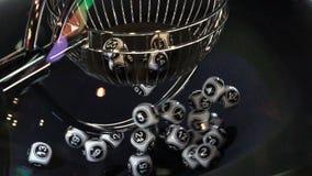 Γραπτές σφαίρες λαχειοφόρων αγορών σε μια περιστρεφόμενη μηχανή bingo κίνηση αργή απόθεμα βίντεο