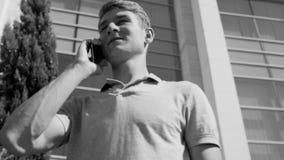 Γραπτή άποψη ενός ατόμου που μιλά από το κινητό τηλέφωνο στο υπόβαθρο της οικοδόμησης φιλμ μικρού μήκους