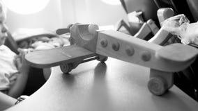 Γραπτή εικόνα κινηματογραφήσεων σε πρώτο πλάνο του ξύλινου μικροσκοπικού αεροπλάνου ενάντια στο φωτιστικό στοκ φωτογραφίες