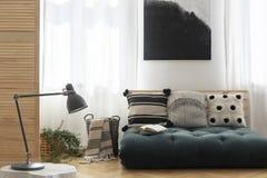Γραπτή ζωγραφική επάνω από το Σκανδιναβικό futon με τα μαξιλάρια στην καθιερώνουσα τη μόδα εσωτερική, πραγματική φωτογραφία καθισ στοκ εικόνες με δικαίωμα ελεύθερης χρήσης
