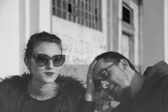 Γραπτή νέα γυναίκα πορτρέτου που αγνοεί το συνεργάτη ανδρών της που φορά τα γυαλιά ηλίου Στοκ εικόνες με δικαίωμα ελεύθερης χρήσης
