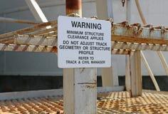 Γραπτή προειδοποίηση - η ελάχιστη εκκαθάριση δομών εφαρμόζει το σημάδι Στοκ Φωτογραφία