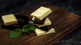 Γραπτή σοκολάτα στο σκοτεινό ξύλινο υπόβαθρο Στοκ εικόνα με δικαίωμα ελεύθερης χρήσης