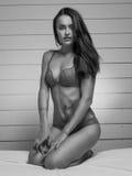 Γραπτή φωτογραφία της νέας όμορφης γυναίκας brunette που φορά την προκλητική lingerie συνεδρίαση στο κρεβάτι και που εξετάζει τη  Στοκ Εικόνα