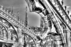 Γραπτή φωτογραφία των άσπρων μαρμάρινων αγαλμάτων, των κώνων και των γλυπτών πετρών στη στέγη του διάσημου καθεδρικού ναού Duomo Στοκ φωτογραφίες με δικαίωμα ελεύθερης χρήσης