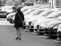 Γραπτή ψωνίζοντας νέα γυναίκα αυτοκινήτων που επιλέγει το αυτοκίνητο σε μια σειρά Στοκ εικόνες με δικαίωμα ελεύθερης χρήσης