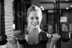 Γραπτός πυροβολισμός της γυναίκας σε βάρη χεριών ανύψωσης γυμναστικής Στοκ Φωτογραφίες