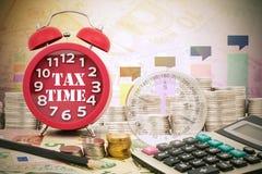 Γραπτός φορολογικός χρόνος λέξης σε ένα ρολόι με την πυξίδα, τα νομίσματα και Calcula Στοκ εικόνα με δικαίωμα ελεύθερης χρήσης