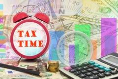 Γραπτός φορολογικός χρόνος λέξης στο ρολόι με την πυξίδα, τα νομίσματα και Calcula Στοκ Εικόνες