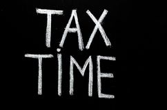 Γραπτός χέρι φορολογικός χρόνος ` φράσης ` στον πίνακα κιμωλίας Στοκ φωτογραφία με δικαίωμα ελεύθερης χρήσης