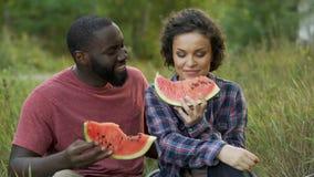 Γραπτό ζεύγος που και που τρώει το εύγευστο καρπούζι απόθεμα βίντεο
