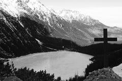 Γραπτό πανόραμα μιας λίμνης βουνών με έναν σταυρό στοκ εικόνες