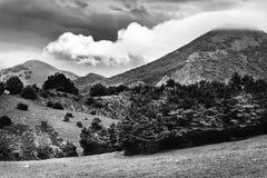 Γραπτό τοπίο με τα βουνά που καλύπτονται με τα μεγάλα σύννεφα Στοκ Φωτογραφία