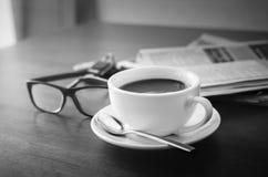 Γραπτό φλυτζάνι καφέ γυαλιών ανάγνωσης εφημερίδων και κινητός Στοκ Εικόνες
