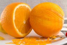 Γρατσουνισμένες πορτοκαλιές και λεπτές μπούκλες της πορτοκαλιάς φλούδας στο άσπρο πιάτο Στοκ φωτογραφία με δικαίωμα ελεύθερης χρήσης