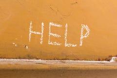 Γραφή βοήθειας με την κιμωλία στο πορτοκαλί υπόβαθρο μετάλλων στοκ εικόνες με δικαίωμα ελεύθερης χρήσης
