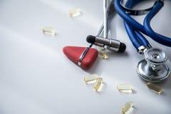 Γραφείο γιατρών νευρολόγων με το στηθοσκόπιο, το ανακλαστικό σφυρί Buck και του Tylor και τα ιατρικά χάπια για τη θεραπεία στοκ εικόνα με δικαίωμα ελεύθερης χρήσης