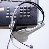 Γραφείο γραφείων με τα αντικείμενα τηλεφώνων και κασκών Στοκ Φωτογραφίες