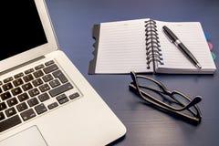 Γραφείο γραφείων με το lap-top και τα γυαλιά Στοκ φωτογραφία με δικαίωμα ελεύθερης χρήσης