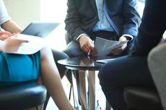 γραφείο διασκέψεων επιχειρησιακών εδρών που απομονώνεται πέρα από το λευκό Κινηματογράφηση σε πρώτο πλάνο των νέων που κάθονται σ Στοκ εικόνα με δικαίωμα ελεύθερης χρήσης