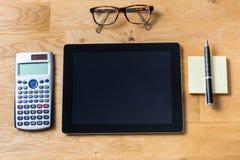 Γραφείο εργασίας με την ταμπλέτα, τα γυαλιά, τον υπολογιστή και το σημειωματάριο σε ξύλινο στοκ φωτογραφία