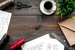 Γραφείο εργασίας ραφτών ` s Σχέδιο του ιματισμού και των εργαλείων στη σκοτεινή ξύλινη τοπ άποψη υποβάθρου copyspace Στοκ Εικόνες
