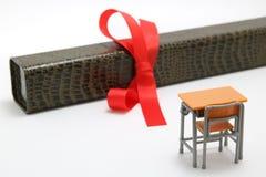Γραφείο και δίπλωμα μελέτης με μια κόκκινη κορδέλλα στο άσπρο υπόβαθρο Στοκ Εικόνα