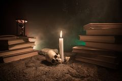 Γραφείο μάγου Ένα γραφείο αναμμένο από το φως κεριών Ένα ανθρώπινο κρανίο, παλαιά βιβλία στην επιφάνεια άμμου Υπόβαθρο ακόμα-ζωής Στοκ φωτογραφίες με δικαίωμα ελεύθερης χρήσης
