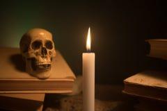 Γραφείο μάγου Ένα γραφείο αναμμένο από το φως κεριών Ένα ανθρώπινο κρανίο, παλαιά βιβλία στην επιφάνεια άμμου Υπόβαθρο ακόμα-ζωής Στοκ Εικόνες