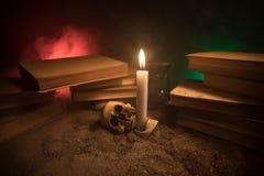 Γραφείο μάγου Ένα γραφείο αναμμένο από το φως κεριών Ένα ανθρώπινο κρανίο, παλαιά βιβλία στην επιφάνεια άμμου Υπόβαθρο ακόμα-ζωής Στοκ φωτογραφία με δικαίωμα ελεύθερης χρήσης