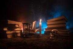 Γραφείο μάγου Ένα γραφείο αναμμένο από το φως κεριών Ένα ανθρώπινο κρανίο, παλαιά βιβλία στην επιφάνεια άμμου Υπόβαθρο ακόμα-ζωής Στοκ Φωτογραφία