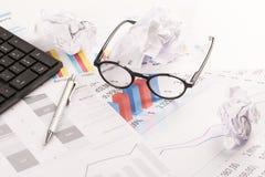 Γραφείο με τις γραφικές παραστάσεις, το πληκτρολόγιο, τα γυαλιά, τη μάνδρα και τα τεμαχισμένα έγγραφα Στοκ φωτογραφία με δικαίωμα ελεύθερης χρήσης