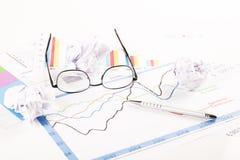Γραφείο με τις γραφικές παραστάσεις, το πληκτρολόγιο, τα γυαλιά, τη μάνδρα και τα τεμαχισμένα έγγραφα Στοκ Εικόνα