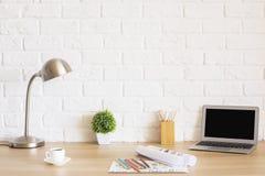 Γραφείο με το lap-top και τα σκίτσα Στοκ Φωτογραφία