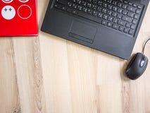 Γραφείο, lap-top και κόκκινο σημειωματάριο στον πίνακα την εργάσιμη ημέρα Στοκ Εικόνες
