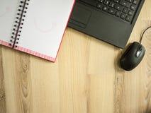 Γραφείο, lap-top, κόκκινο σημειωματάριο στον πίνακα την εργάσιμη ημέρα Στοκ Φωτογραφίες